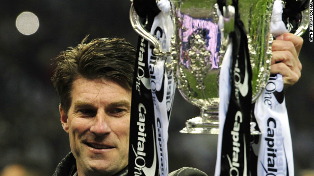 Swansea manager Michael Laudrup gets his hands on the English League Cup after his side's 5-0 final win over Bradford at Wembley.