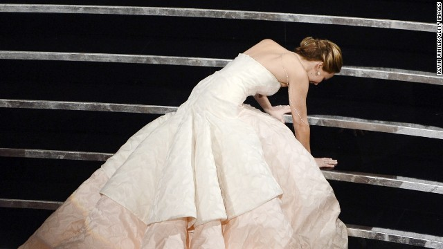 "Jennifer Lawrence trips on her way to the stage after winning best actress for ""Silver Linings Playbook."""
