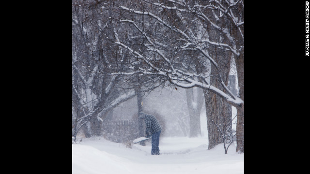 A resident shovels snow as the wind cuts down on visibility during a winter storm in Denver on Sunday, February 24.