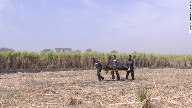 An ambulance crew carries the body of a tourist who died in the crash.