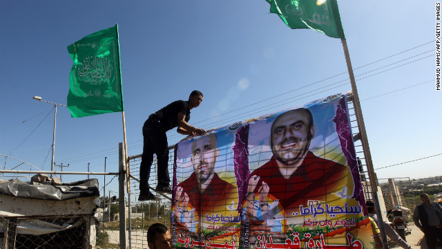 Palestinians erect posters of hunger-striking Palestinian prisoners at Erez border crossing between Israel and the northern Gaza Strip on February 26, 2013.