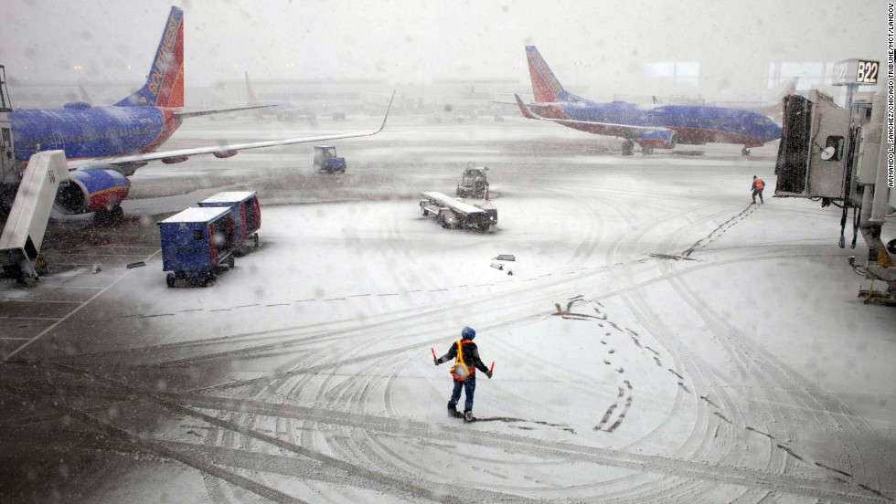 Southwest Airlines employees guide a plane into the gate at Midway International Airport in Chicago on Tuesday, February 26. Back-to-back storms have hit the Great Plains, which is still digging out from last week's weather. <i>Are you experiencing the storm? If it's safe, </i><i><a href='http://ireport.cnn.com/topics/877827'>share your photos</a></i>.