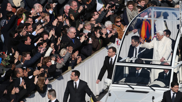 Benedict waves to the crowd as he arrives in the popemobile.