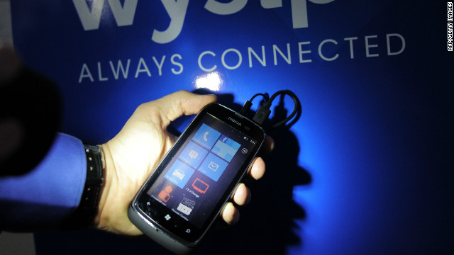 A worker of Wysips shines a torch on the screen of a prototype of a smartphone equipped with a photovoltaic film.