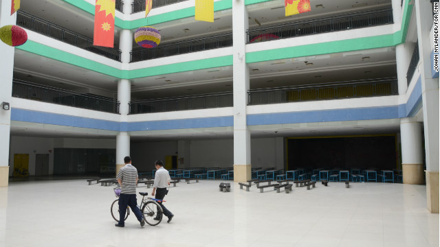 Two men walking through the empty mall in a space planned for restaurants.
