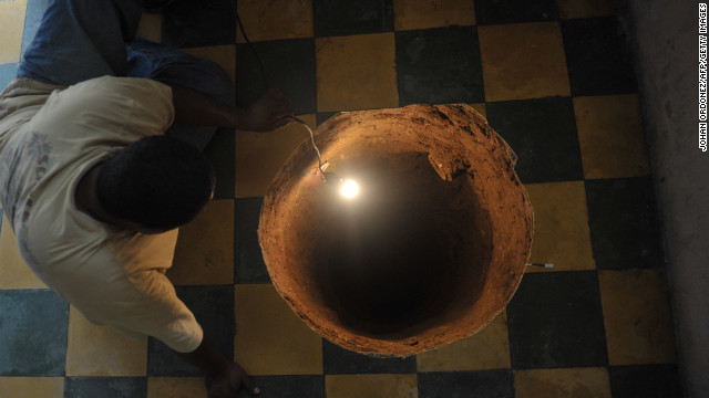 A man inspects a 40-foot-deep sinkhole that a family found after they heard a loud booming noise in their kitchen in July 2011, in Guatemala City.