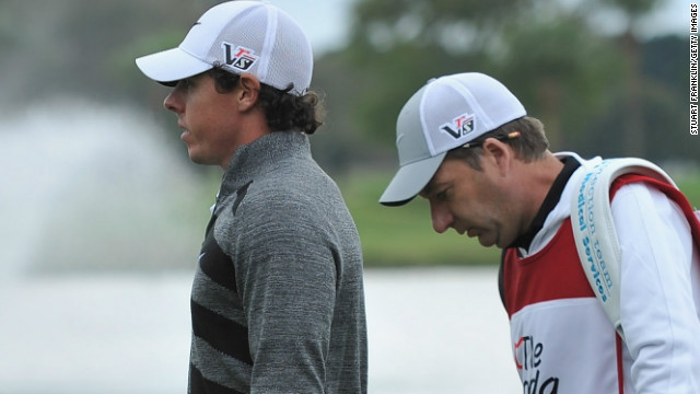 Rory McIlroy and his caddie J.P Fitzgerald walk off the course after the Northern Irish stars pulls out of the second round of the Honda Classic. 