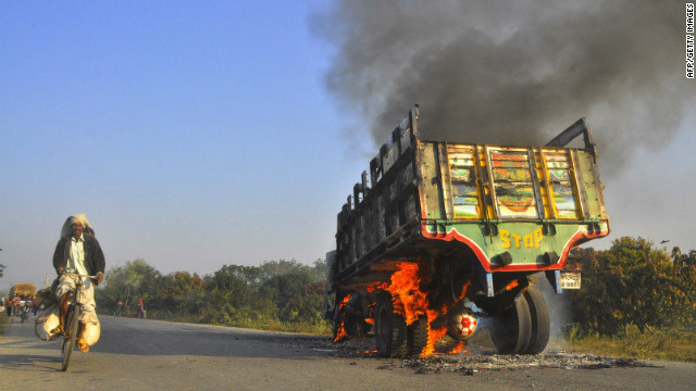 A bus set on fire by Islamist activists burns on a street as a man rides his bicycle in Rajshahi northwest from Dhaka.