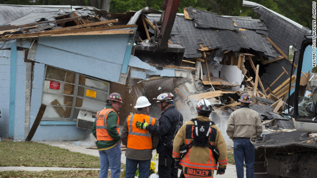 Workers watch the demolition of the house where a sinkhole opened beneath the bedroom of Jeff Bush three days before in Seffner, Florida, on Sunday, March 3. Sinkholes caused by acidic groundwater corroding the limestone or carbonate rock underground are common in Florida, according to the Florida Department of Environmental Protection.