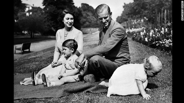 Elizabeth and Philip sit in the grass with their two children, Charles, Prince of Wales, and Princess Anne, circa 1951. They later had two more children, Edward, Earl of Wessex, and Andrew, Duke of York.
