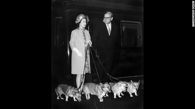 Queen Elizabeth II arrives at King's Cross railway station in London with her four Corgis in October 1969 after vacationing at Balmoral Castle in Scotland.