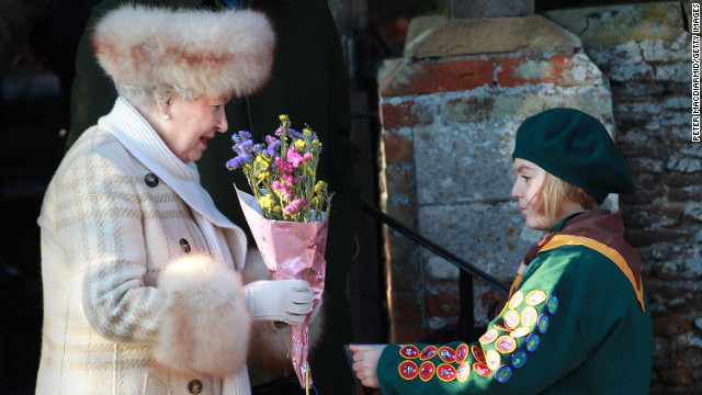 Elizabeth receives flowers from a Girl Guide after attending the Christmas Day church service at St Mary's Church in Sandringham, England, in 2010.