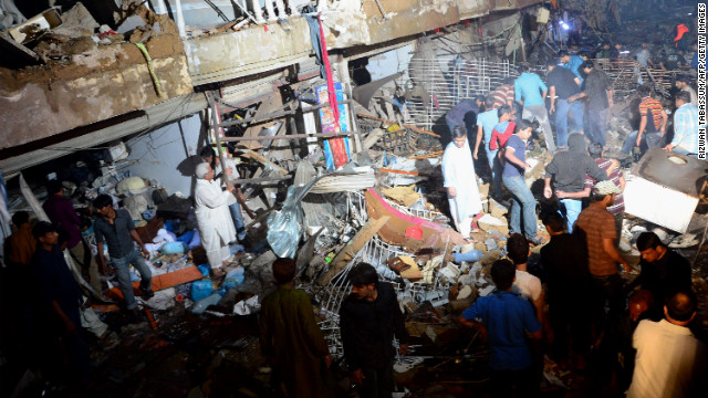 Pakistani rescue workers and citizens go through the debris.