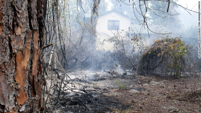 Scorched property surrounds an untouched house in the Ocala National Forest just south of Salt Springs, Florida, on Sunday.