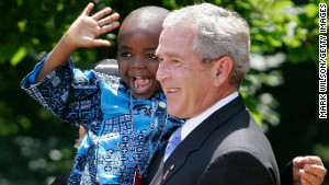President George W. Bush holds up 4-year-old Baron Tantoh during a news conference on PEPFAR.
