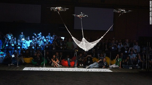 Quadrocopters learn how to perform tasks using algorithms created by ETH Zurich. Here, three machines can been seen working together to cradle a ball in a net ...