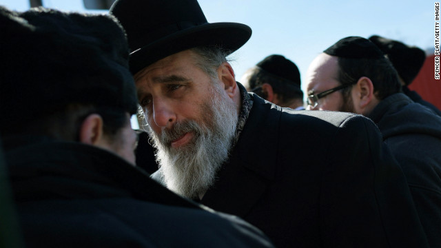 Two members of the Brooklyn Orthodox Jewish community talk before the news conference on Monday.