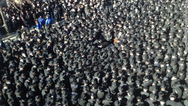 Mourners attend the funeral for Raizel Glauber and her husband, Nathan Glauber, in Brooklyn, on Sunday.