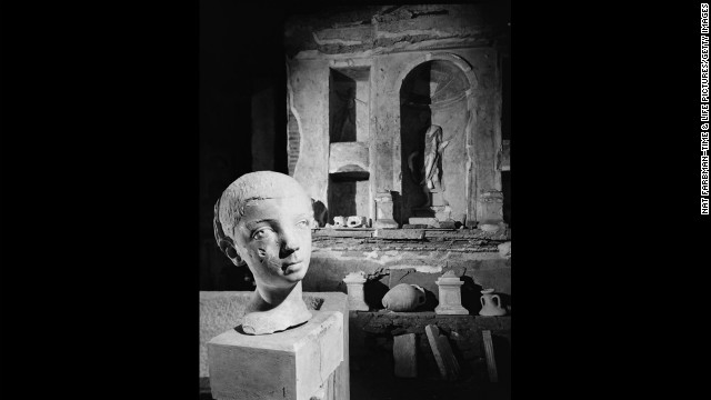 The bust of a statue is seen during the excavating process.