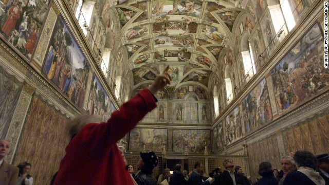 Journalists view the unveiling of the latest Sistine Chapel restoration on December 10, 1999.