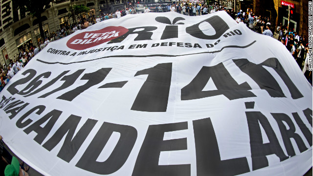 People hold a huge banner during a demonstration demanding that Brazilian President Dilma Roussef veto a bill that would redistribute oil royalties in favor of non-oil producing states.