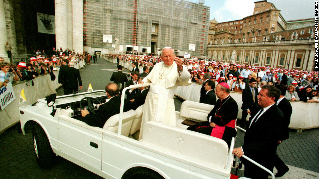 Pope John Paul II salutes the crowd as he arrives for his weekly address in Vatican City on May 27, 1998.