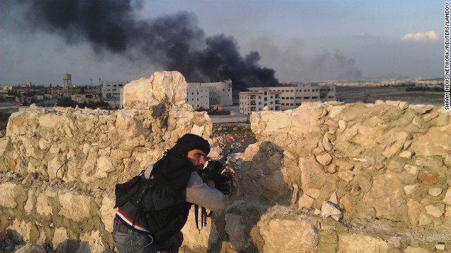 A Free Syrian Army fighter looks back as smoke rises during fighting between rebel fighters and forces loyal to Syria's President Bashar al-Assad on the outskirts of Aleppo on Saturday, March 2. 