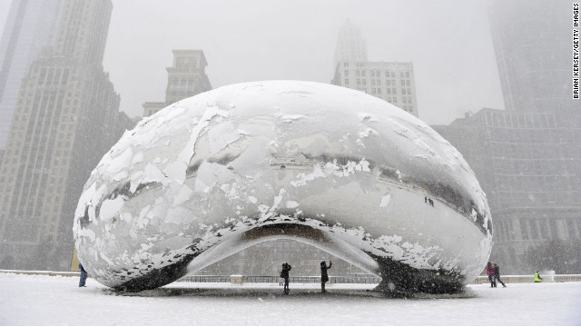"People stand under the snow-covered ""Cloud Gate"" sculpture, commonly known as ""the bean,"" on Tuesday, March 5, in Chicago, Illinois."