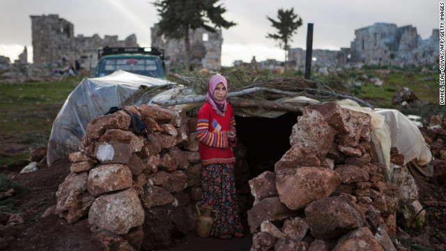 A Syrian girl stands at the entrance of a makeshift home near ruins in the ancient city of Serjilla in northwestern Syria on February 11. About half of Syria's refugees are children.