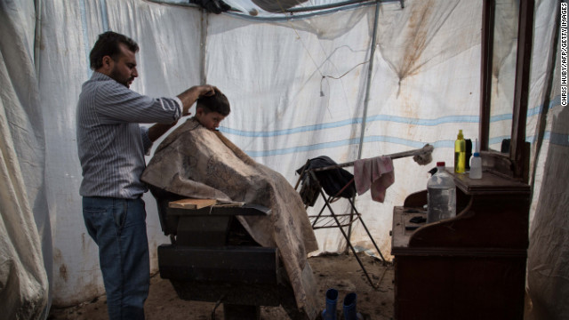 A child gets a haircut at a makeshift barbershop at the Azaz refugee camp in February 2013.