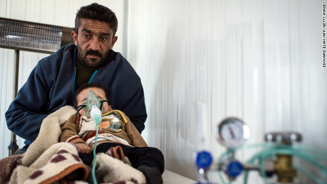 A refugee visits a clinic with his child at the Azaz refugee camp on February 10.