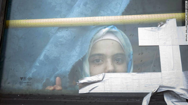 A Syrian girl looks through the window of a bus where she has lived with her family for the past eight months at a refugee camp in Bab al-Salam on the Syria-Turkey border on February 28.