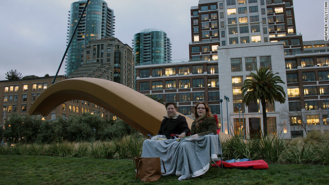 San Francisco residents cozy up with a picnic to watch the Bay Bridge light up.