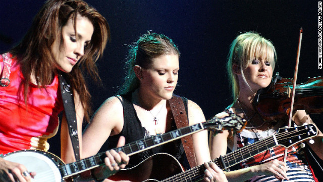 "In March 2003, Dixie Chicks frontwoman Natalie Maines said to a London audience, ""Just so you know, we're on the good side with y'all. We do not want this war, this violence. And we're ashamed the president of the United States is from Texas."" That comment led to nationwide backlash and the band has not had a single chart the top 30 since. In this photograph, the Dixie Chicks perform live on stage at The Point Theatre on September 18, 2003, in Dublin, Ireland."