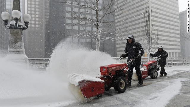 Arturo Garcia, left, and Ricardo Perez clear snow from Chicago's Riverside Plaza on March 5.