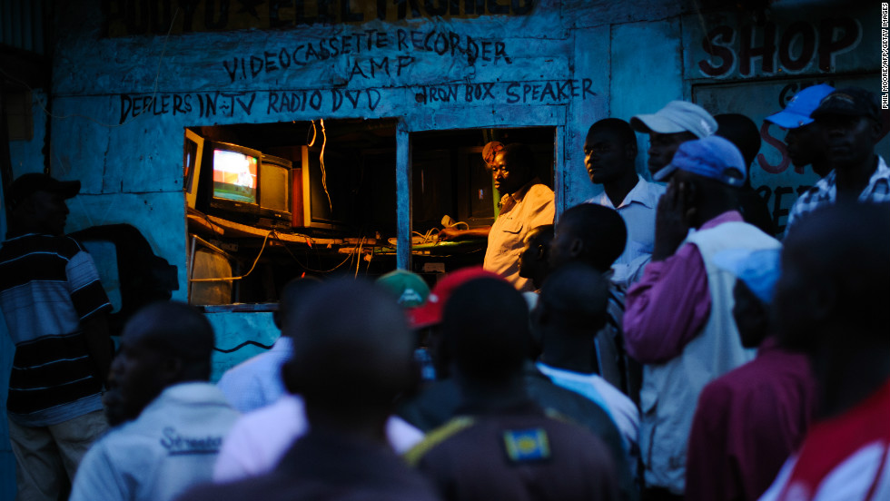 Men watch the incoming provisional election results on a television outside a shop in the Kibera slum of Nairobi, Kenya's capital, March 5, 2013.
