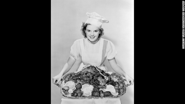 Judy Garland, dressed as Dorothy, poses with a turkey to promote the movie during Thanksgiving.