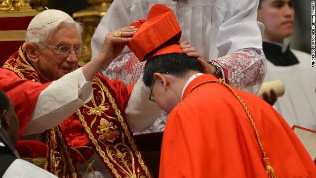 Luis Antonio Tagle of the Philippines, right, receives his biretta hat as Pope Benedict XVI appoints him as a cardinal during a ceremony on November 24, 2012 at St. Peter's Basilica at the Vatican.