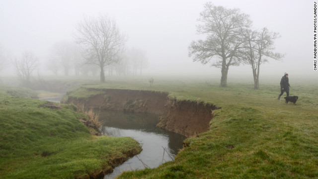 Fog shrouds a dog and its owner as they walk beside Bourne Brook, in Toft Cambridgeshire, United Kingdom, on Friday, March 8. 