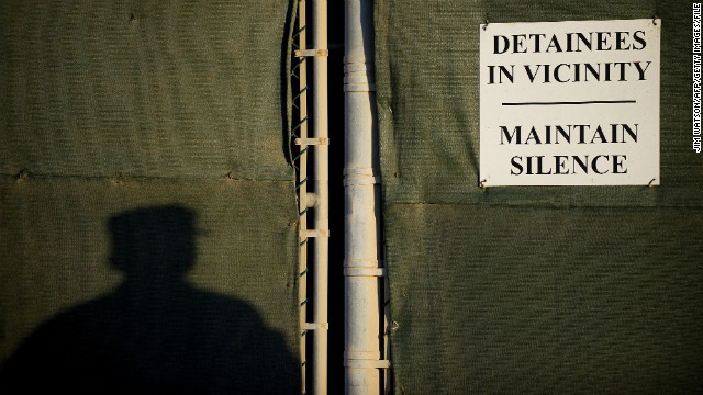 A soldier stands near a placard on the fence line of the detention facility in January 2012. 