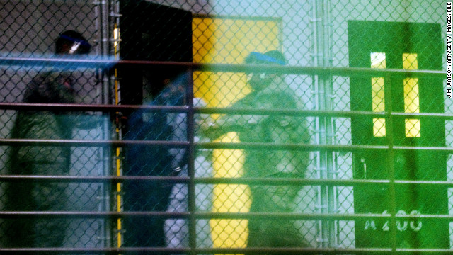 Guards move a detainee from his cell in Cell Block A of the Camp 6 detention facility in January 2012.