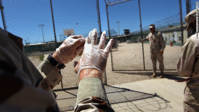 A military guard puts on gloves before moving a detainee within the detention center in September 2010.
