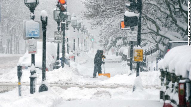 A man shovels snow on Boston's Commonwealth Avenue. Delays of 2.5 hours were reported at Boston's Logan Airport.