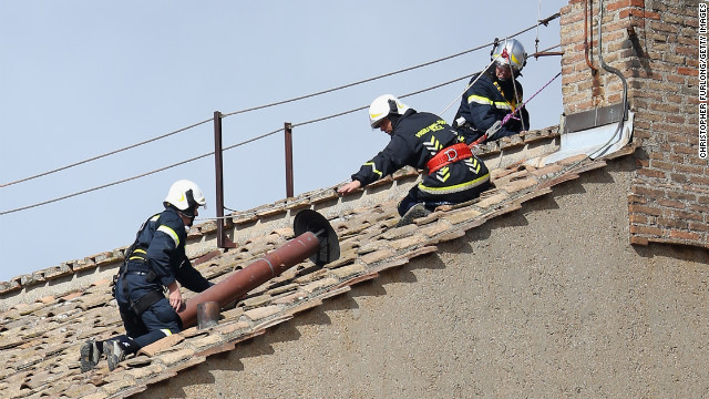 Members of the Vatican Fire Brigade install the chimney on top of the Sistine Chapel on March 9.