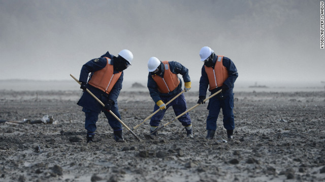 Japanese police officers dig through rubble in Miyagi Prefecture on Sunday.
