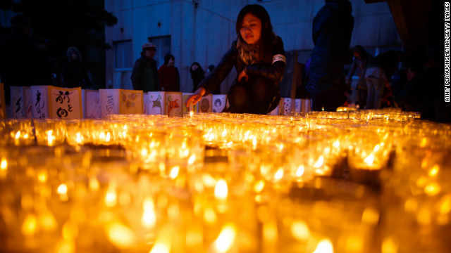 Students and volunteers light candles at Yuriage Junior High School during a commemoration ceremony on Sunday in Natori, Japan.