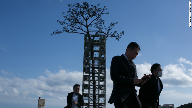"Visitors walk in front of a replica of the ""miracle"" pine tree on Sunday in Rikuzentakata. It was the last surviving pine in what was once a sprawling grove of more than 70,000, standing as a symbol of hope amid the devastation."