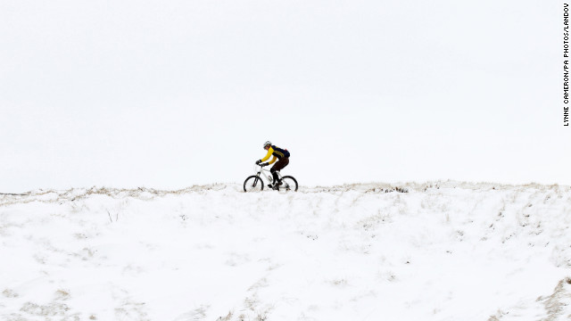 A cyclist makes his way along a snowy track near Ladmanlow, United Kingdom, on March 10 as a return of freezing temperatures and snow delay springtime weather for Great Britain.