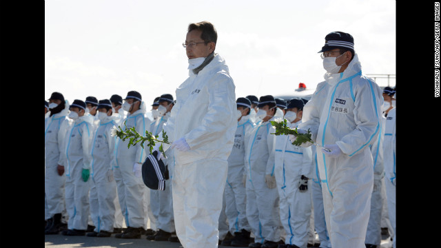 Police officers offer chrysanthemum flowers for tsunami victims in Namie on Monday after their search for remains of those still missing, two years after the disaster.