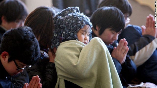 Children pray during a memorial ceremony to mark the second anniversary of the disaster in Kamaishi, Japan, on Monday.